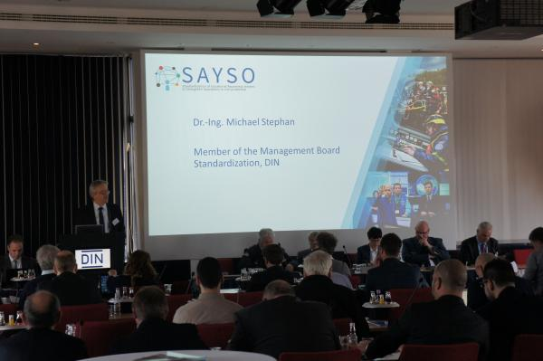 Dr.-Ing. Michael Stephan (DIN), presenting the Deutsches Institut für Normung E.V., host organisation of the SAYSO Public Workshop
